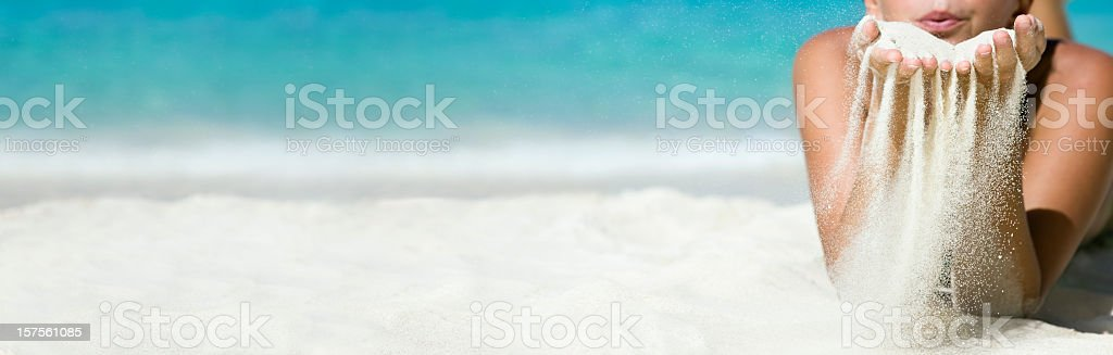woman blowing sand off her hands royalty-free stock photo
