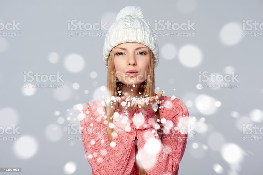 Woman blowing snow at you stock photo