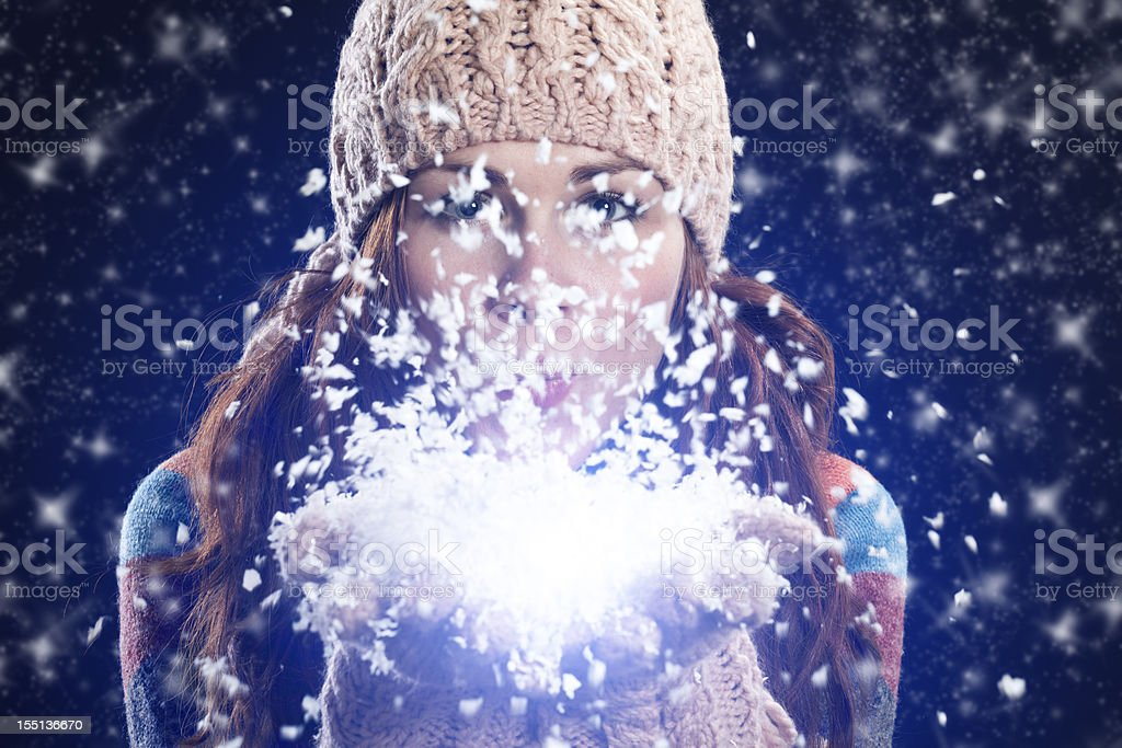 Woman blowing snow from her hands stock photo