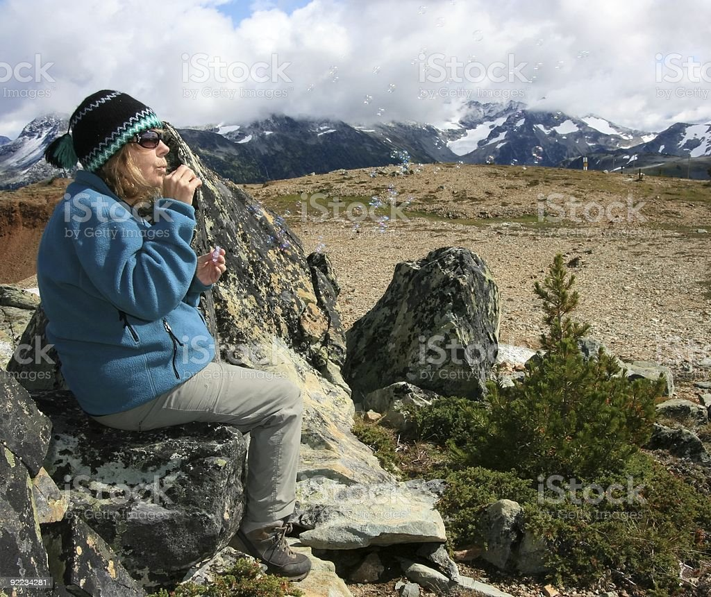 Woman Blowing Soap Bubbles in the Alpine stock photo