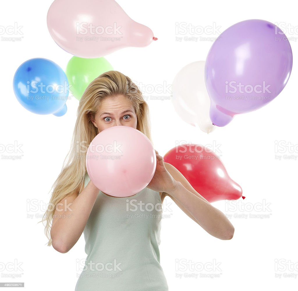 Woman blowing up balloons for a party stock photo