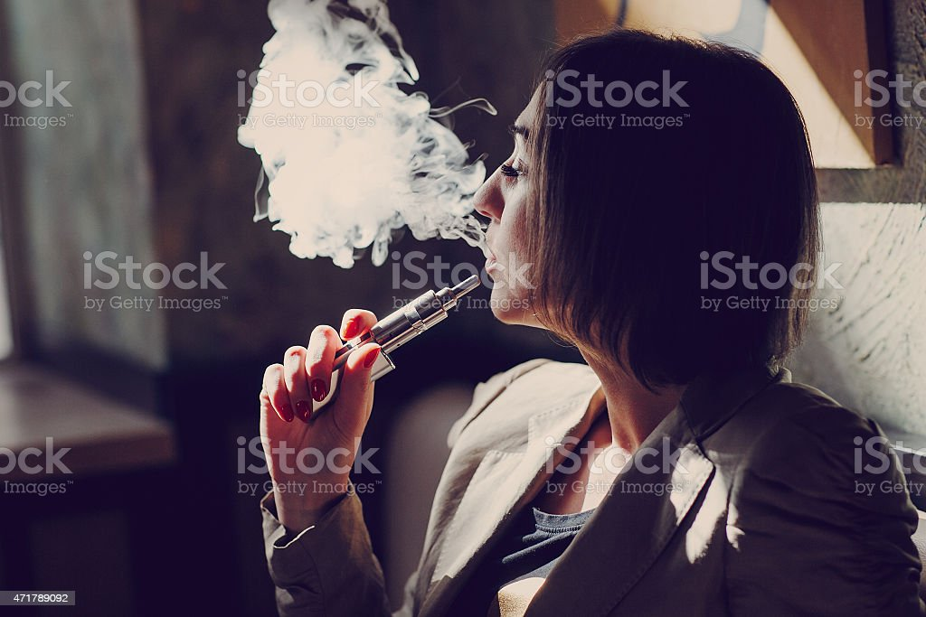 Woman blowing vapors from an electronic cigarette stock photo