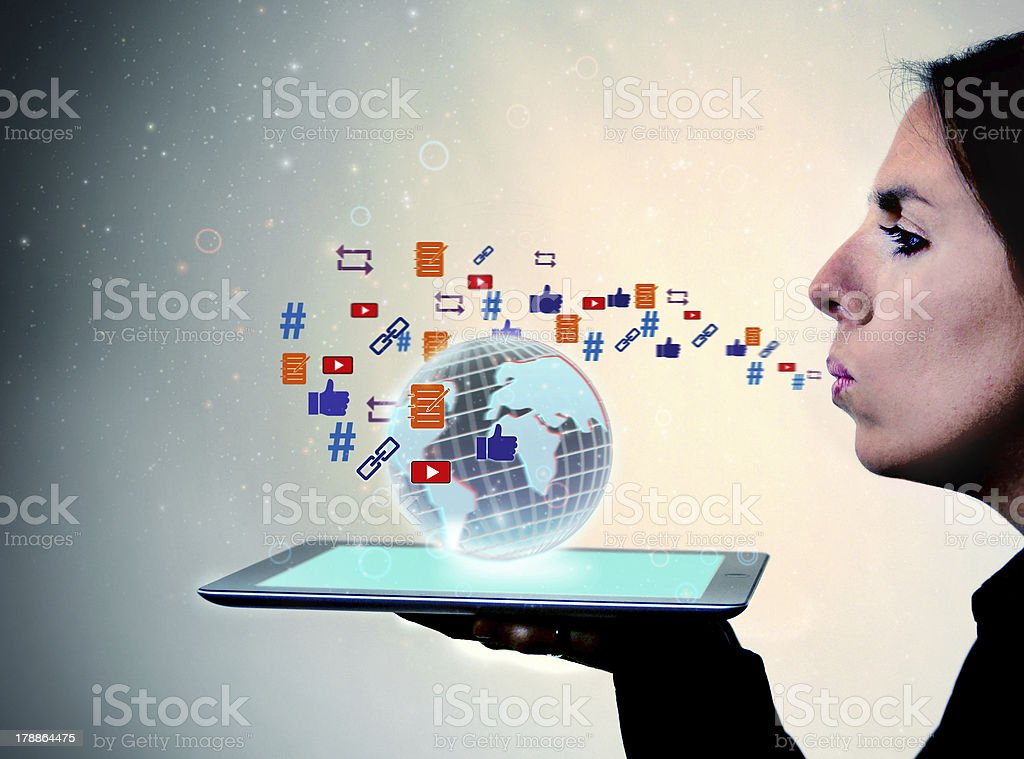 Woman Blows Social Media Icons Across Globe on a Tablet stock photo