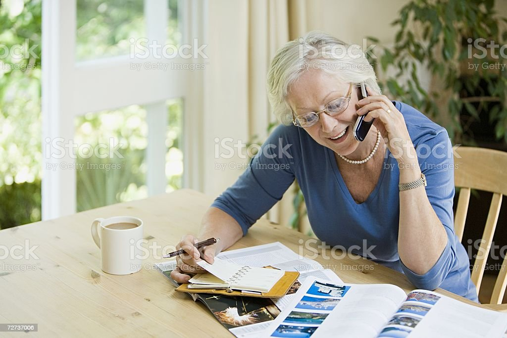 Woman booking a holiday on cell phone stock photo