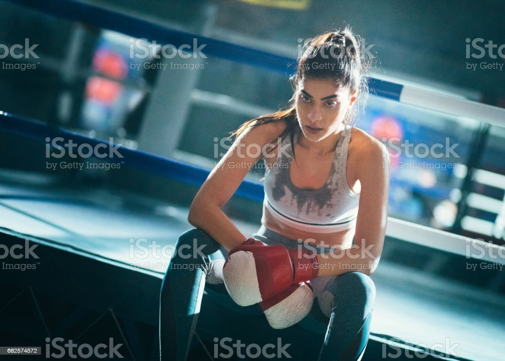 Woman boxer resting after a training session in the ring stock photo