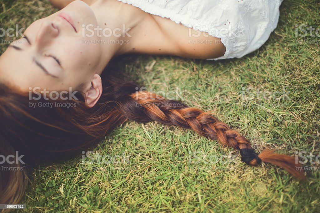 Woman, braid, grass and dreams stock photo
