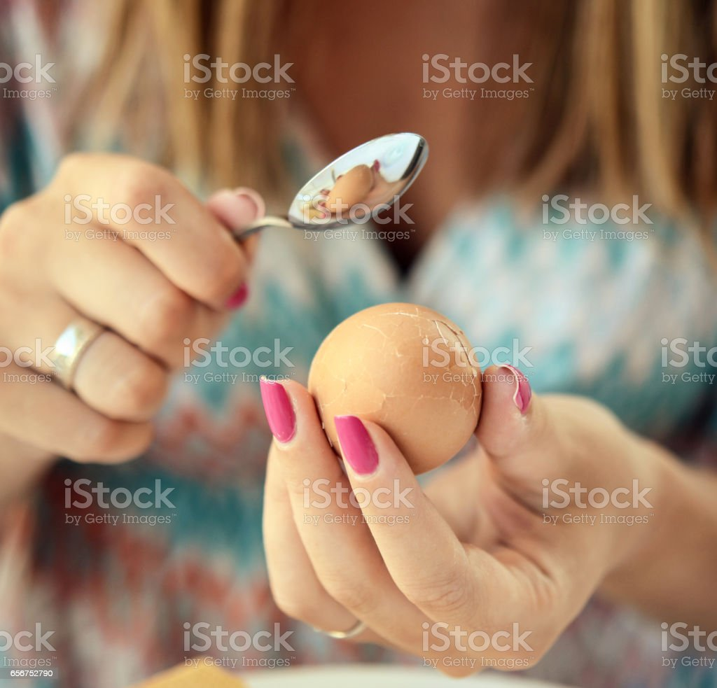 Woman breaking boiled egg with tea spoon stock photo
