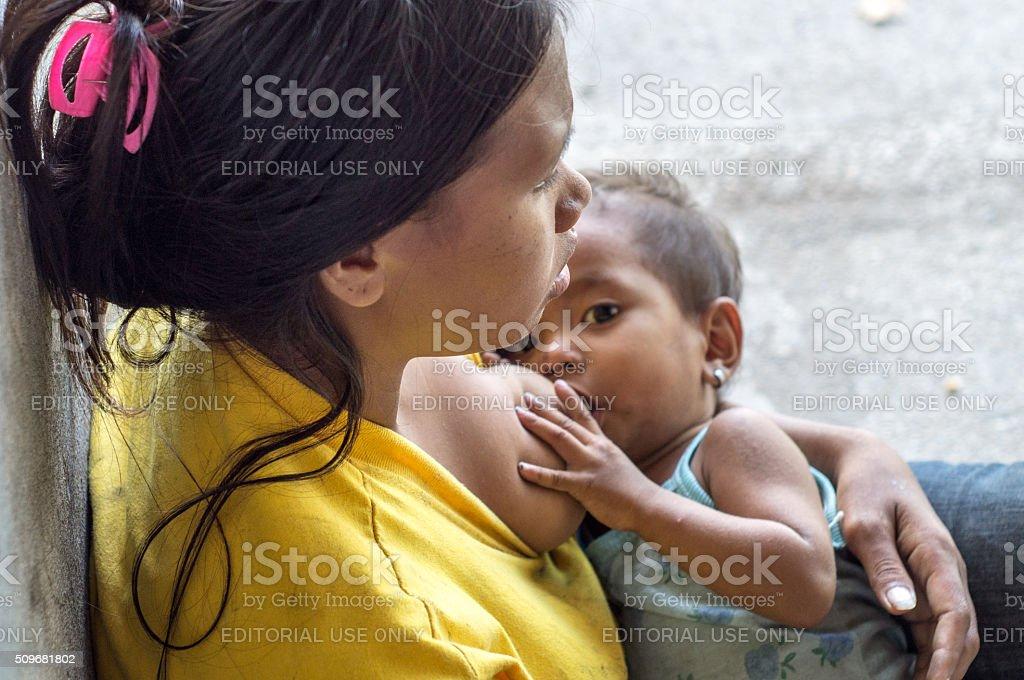 Woman breast feeding a child begging at church portal stock photo