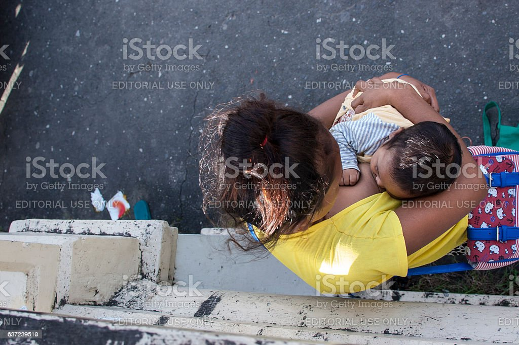 Woman breast feeding a child selling candles stock photo