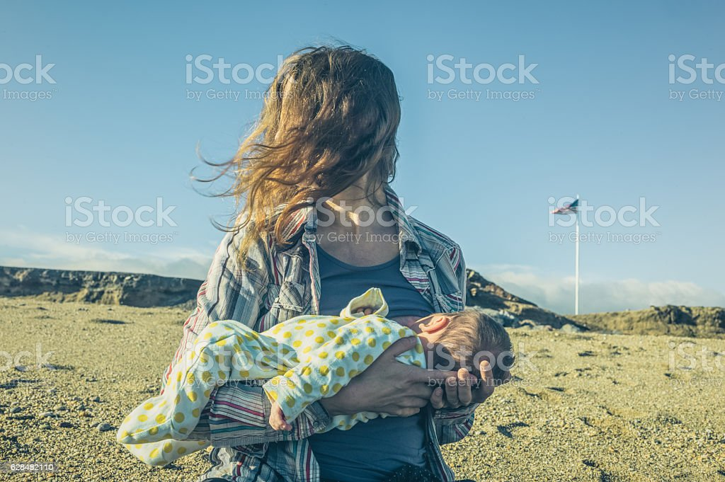 Woman breastfeeding in barren landscape with american flag stock photo