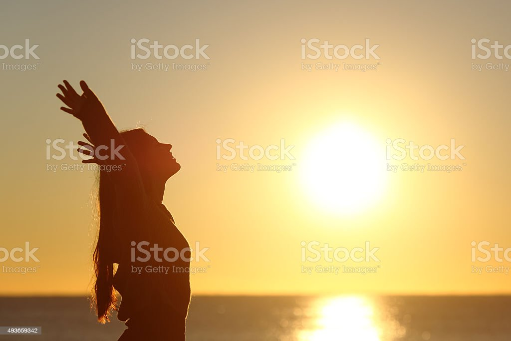 Woman breathing fresh air at sunset stock photo