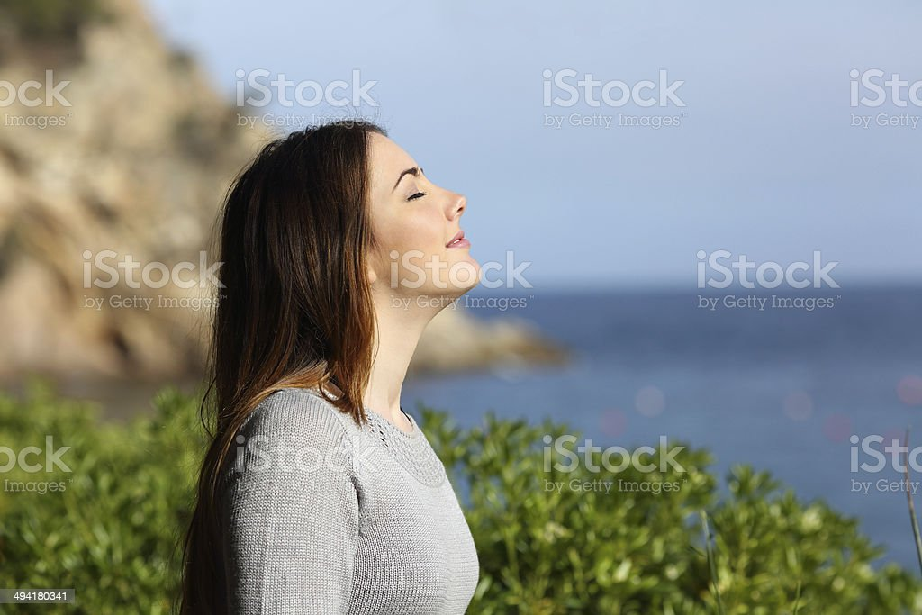 Woman breathing fresh air relaxed on vacation stock photo