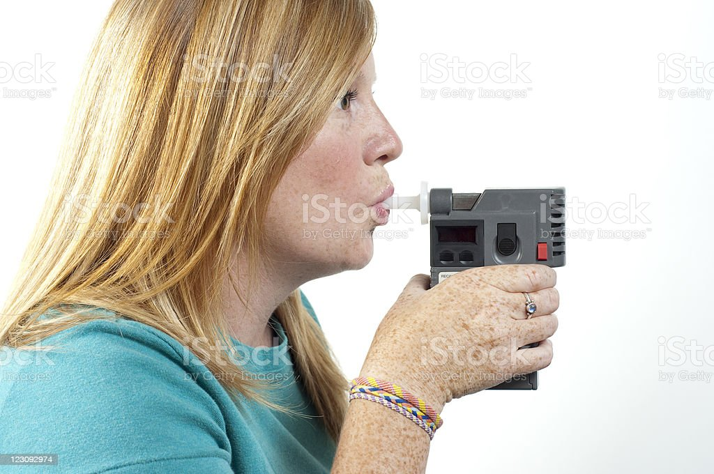 A woman breathing into a breath test stock photo