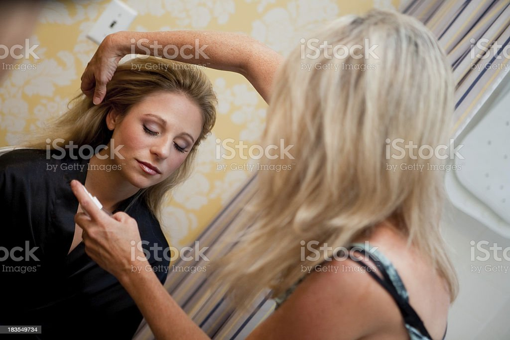 woman bride having her hair done by stylist in preparation stock photo