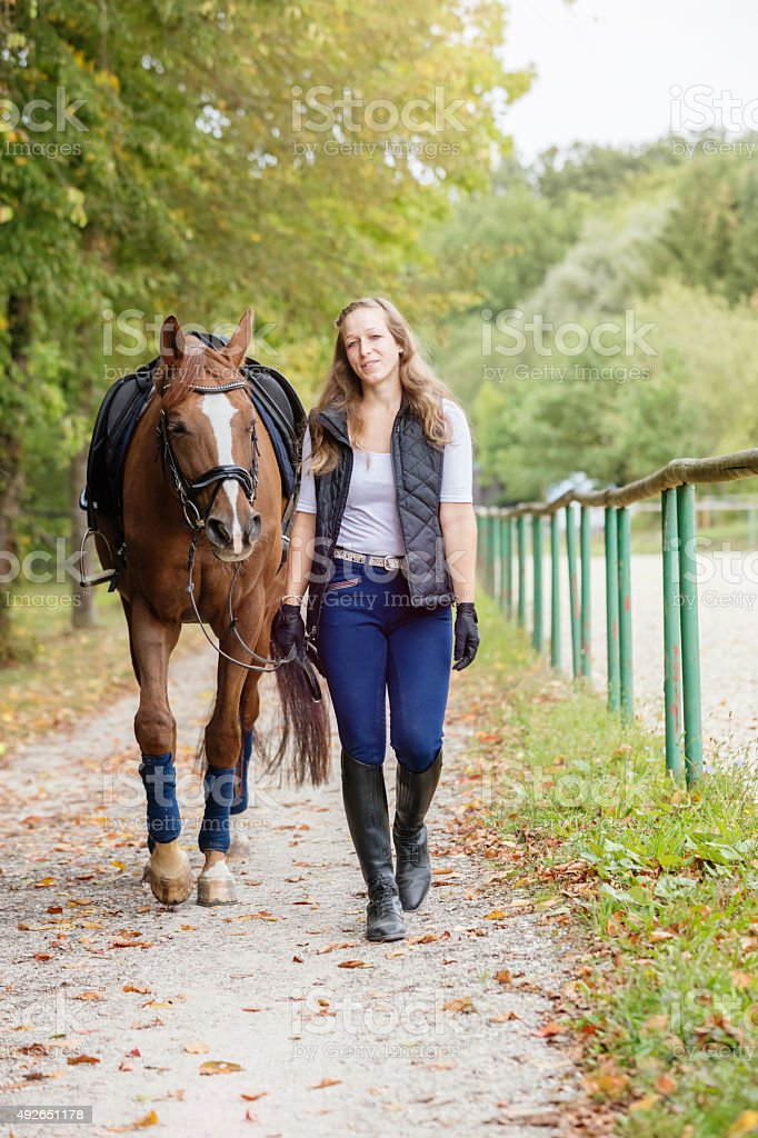 Woman bringing her horse back from the ride stock photo