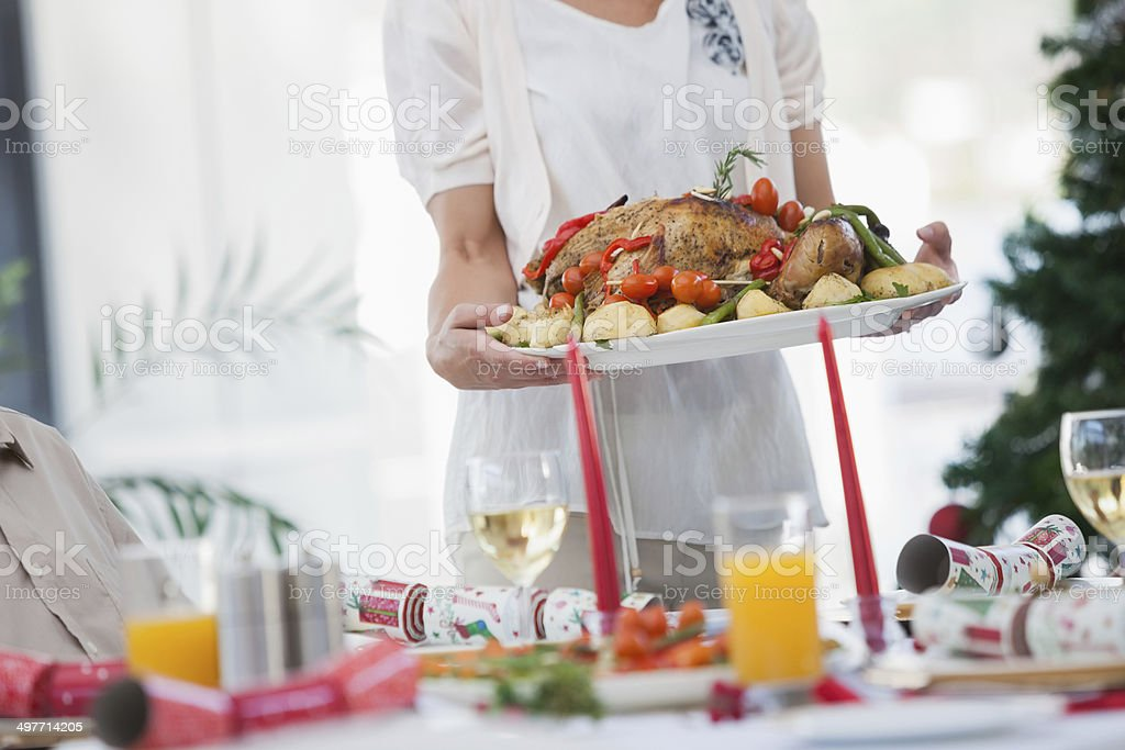 Woman bringing roast chicken at table stock photo