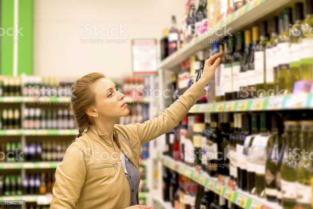 A woman browsing the wine in a supermarket stock photo