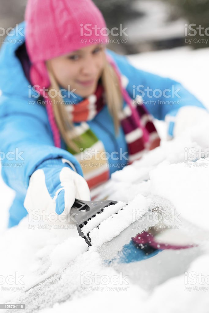 Woman brushing snow from car windscreen winter stock photo