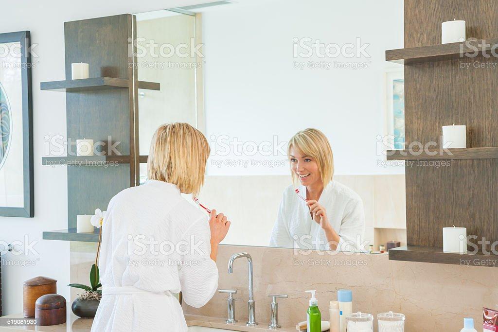 Woman brushing teeth at sink in bathroom stock photo