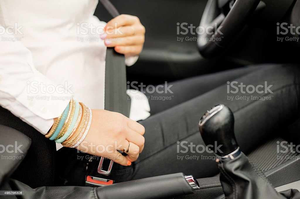 Woman buckling up stock photo