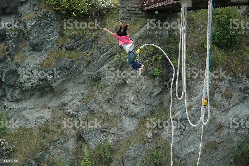 A woman bungee jumping off of a bridge stock photo