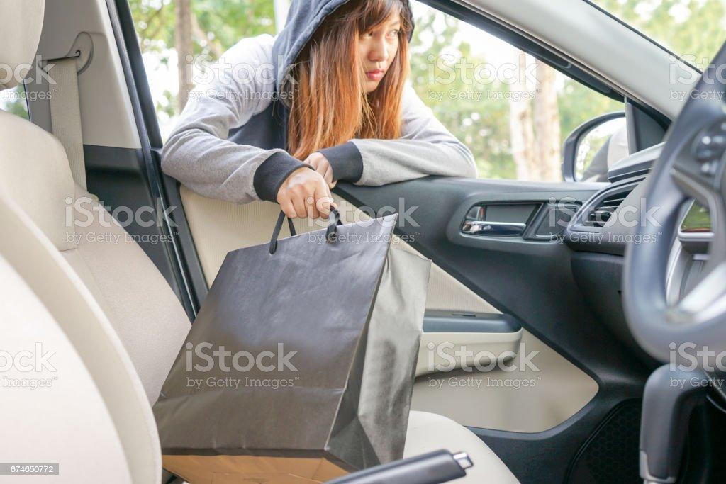 Woman burglar steal a shopping bag through the window of car - theft concept. stock photo