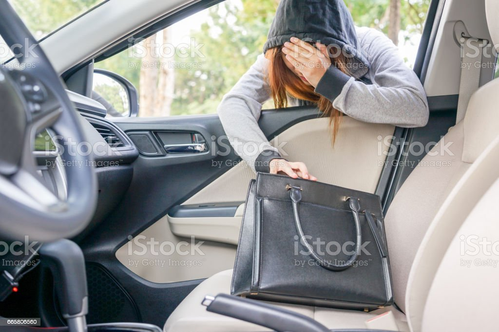Woman burglar steal and look in a shoulder bag through the window of car - theft concept. stock photo
