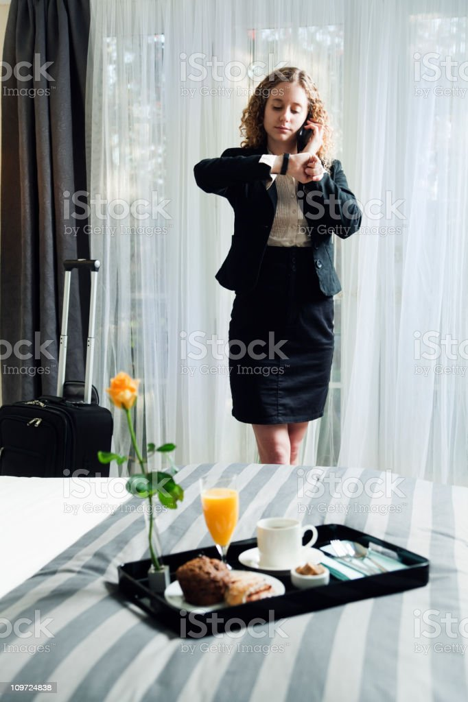 Woman Business Traveler Looking at Her Watch in Hotel Room royalty-free stock photo