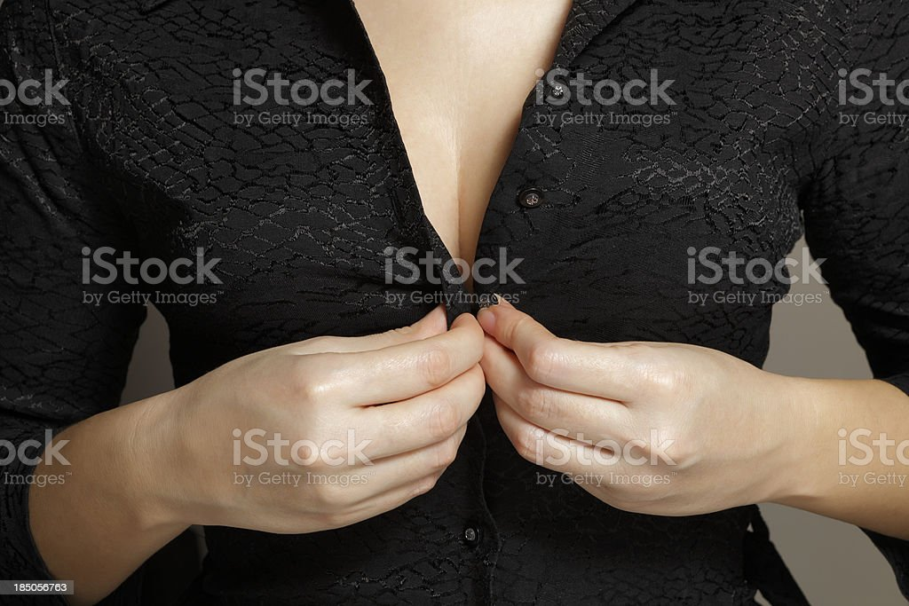 woman buttoning her shirt stock photo