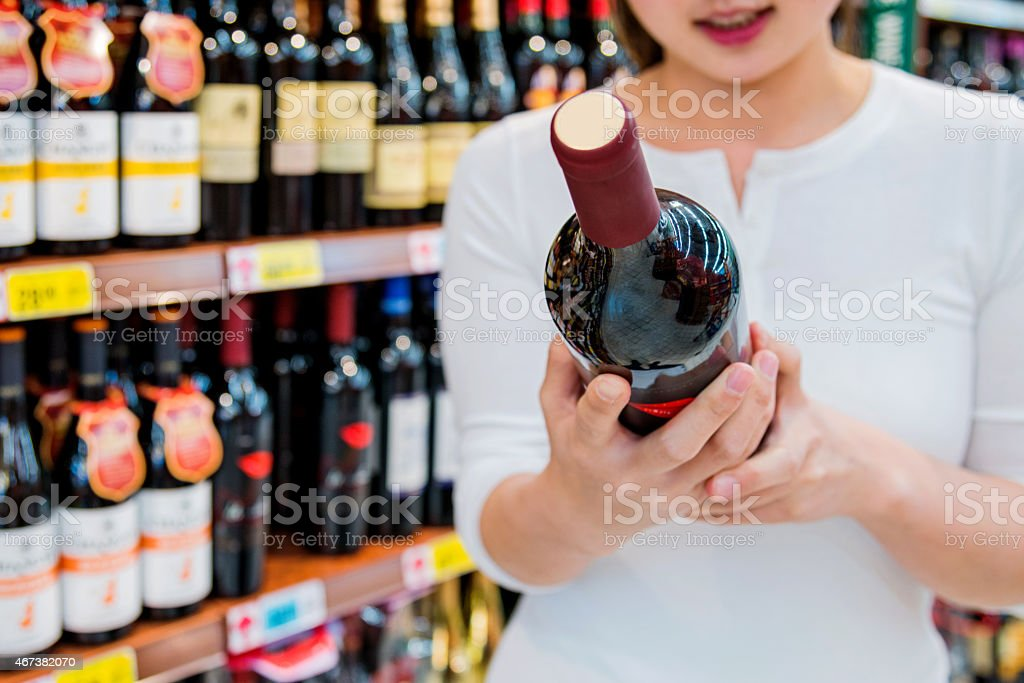 woman buying a bottle of wine stock photo
