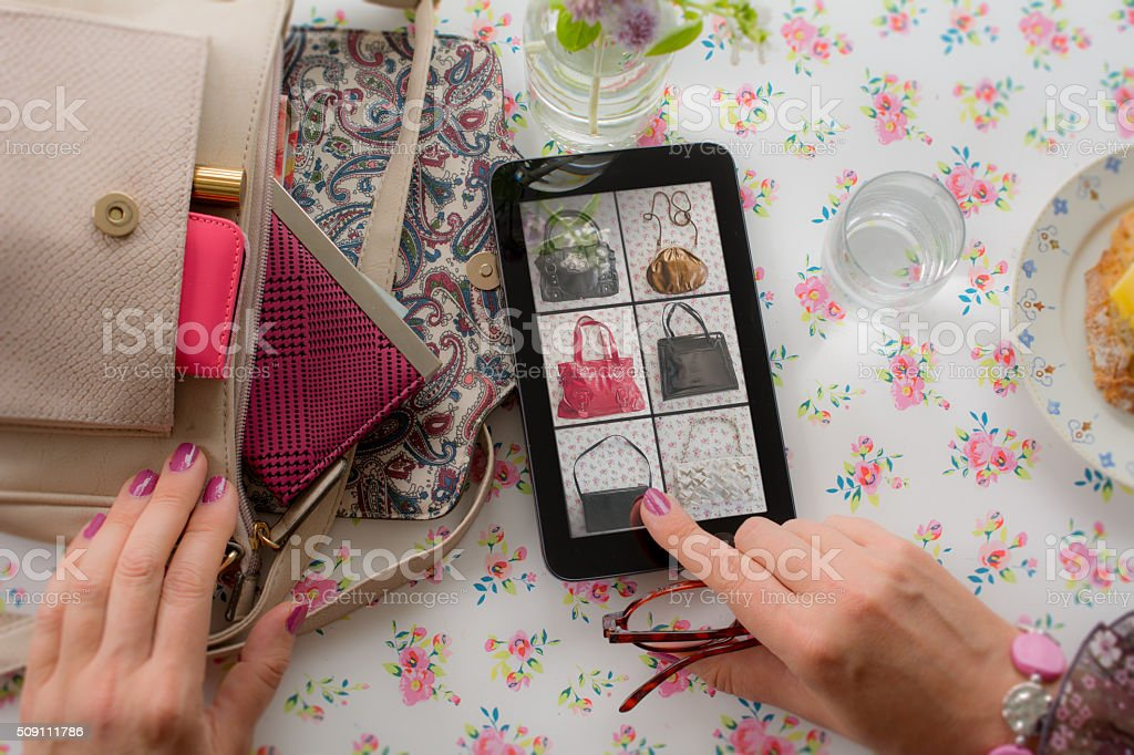 Woman buying a vintage handbag online stock photo