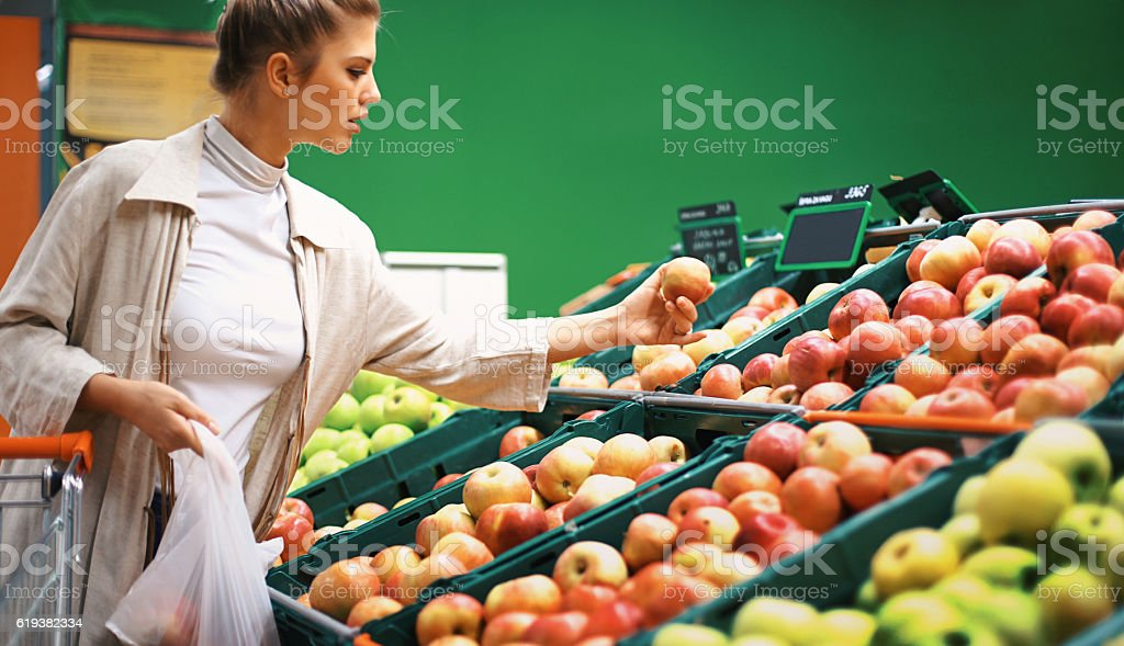 Woman buying apples at a supermarket. stock photo