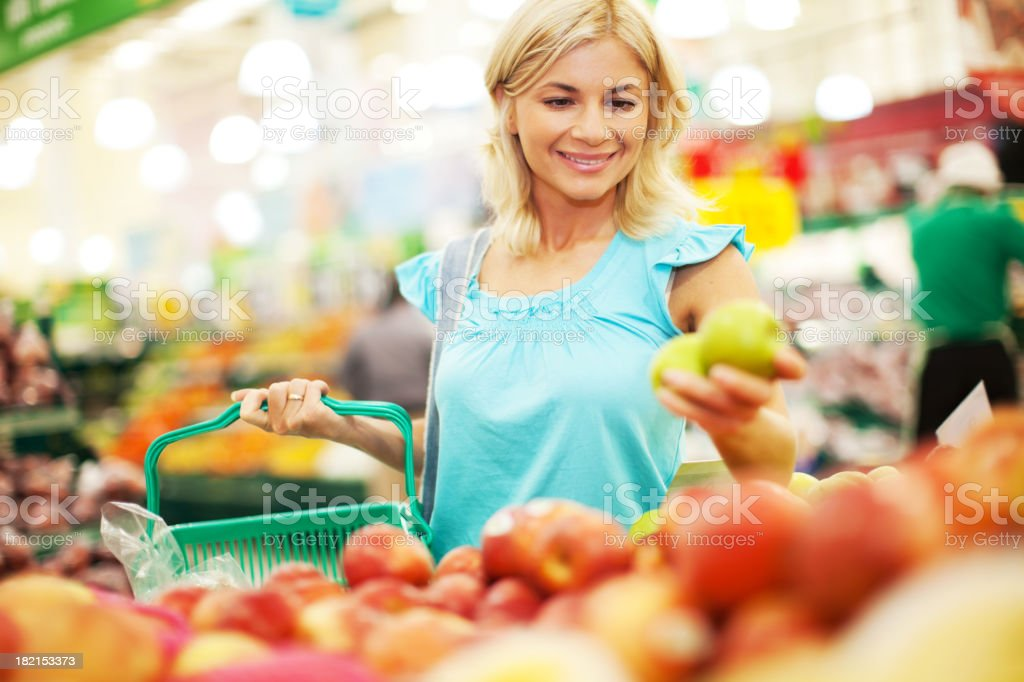 Woman buying apples in the fruit store. stock photo