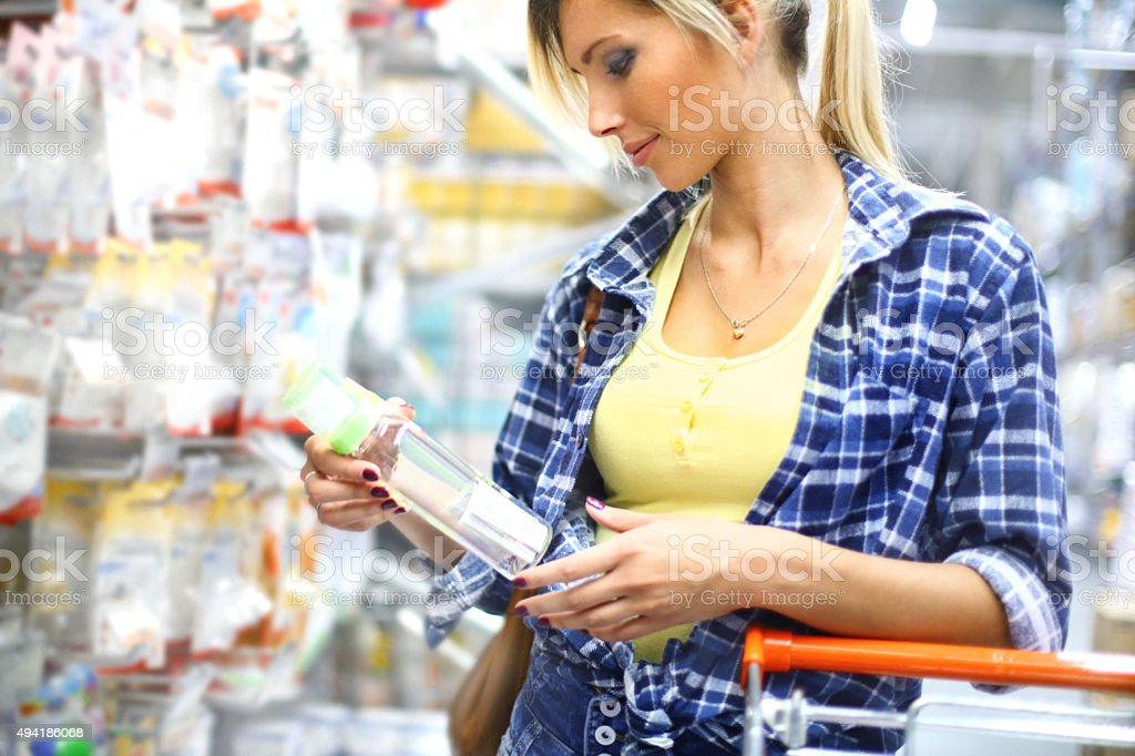 Woman buying baby goods in supermarket. stock photo