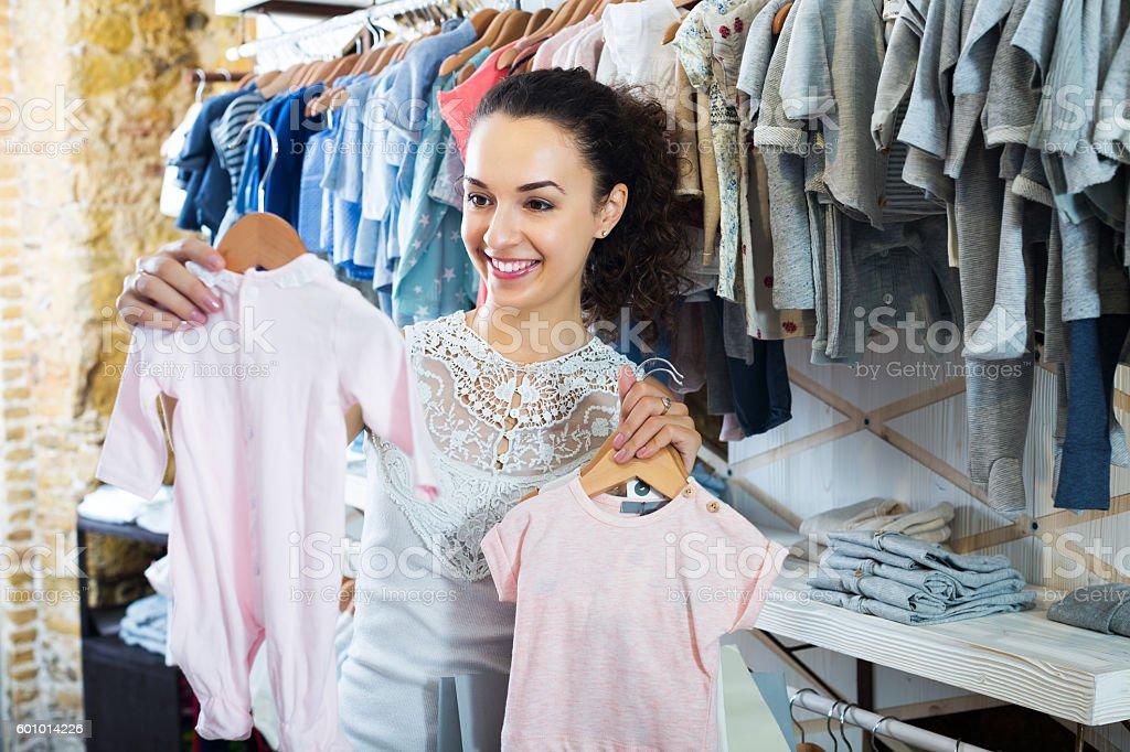 Woman buying baby sleep suit stock photo