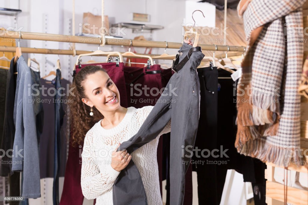 Woman buying breeches at the store stock photo