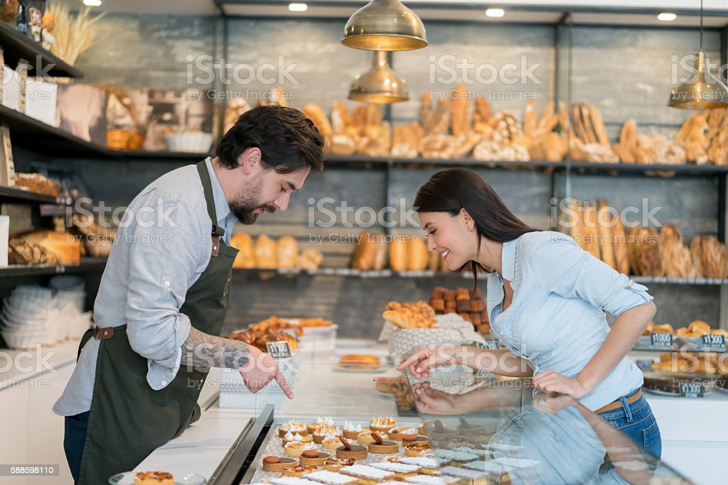 Woman buying cakes at a pastry shop stock photo