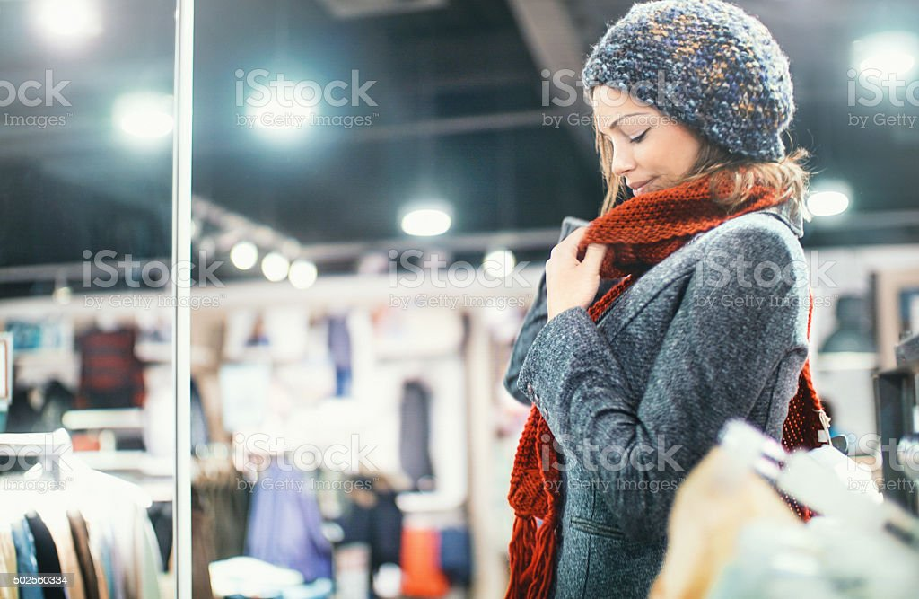 Woman buying clothes at department store. stock photo