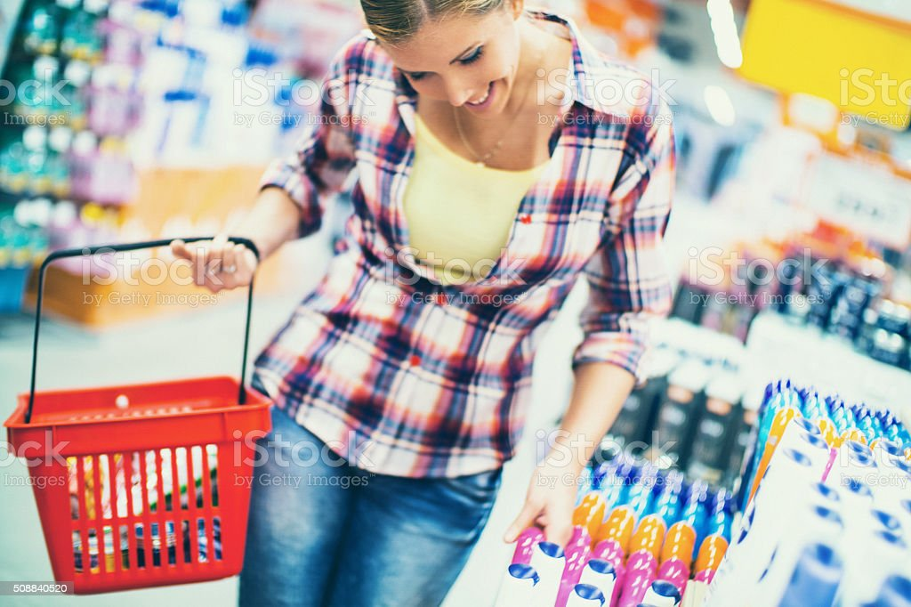 Woman buying cosmetics in supermarket. stock photo