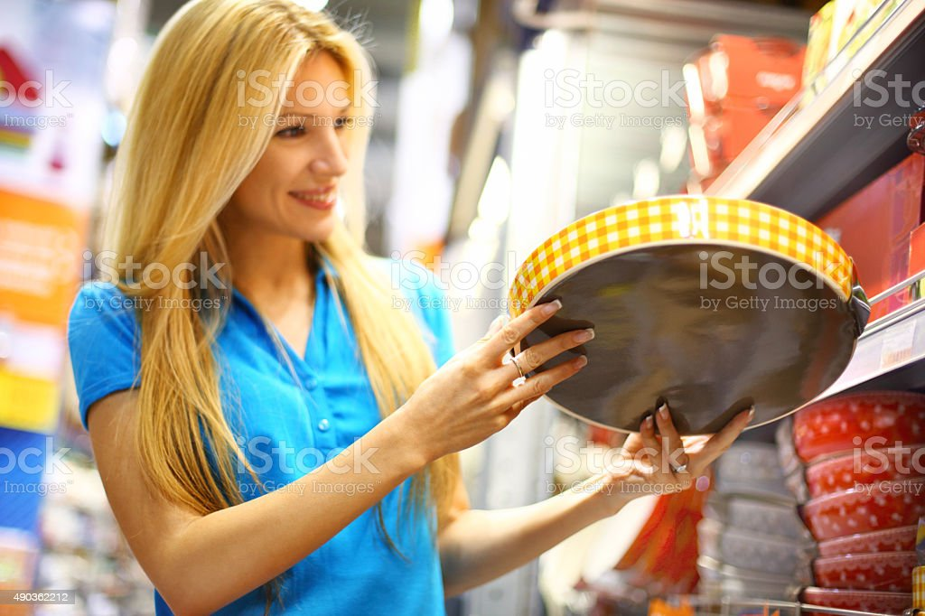 Woman buying dishes in supermarket. stock photo