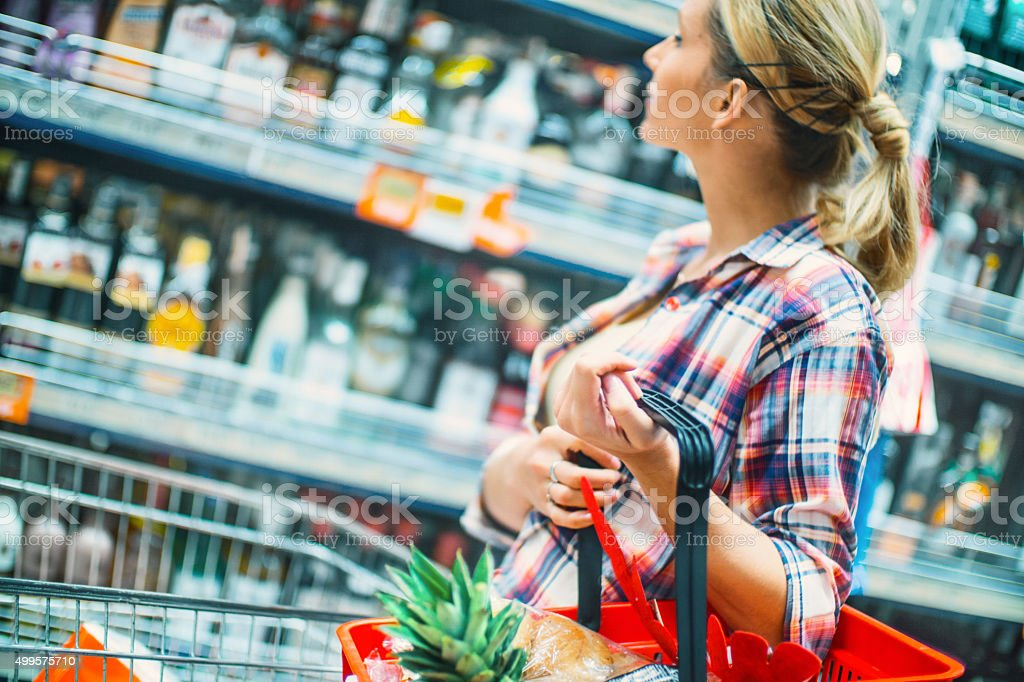 Woman buying drinks in a supermarket. stock photo