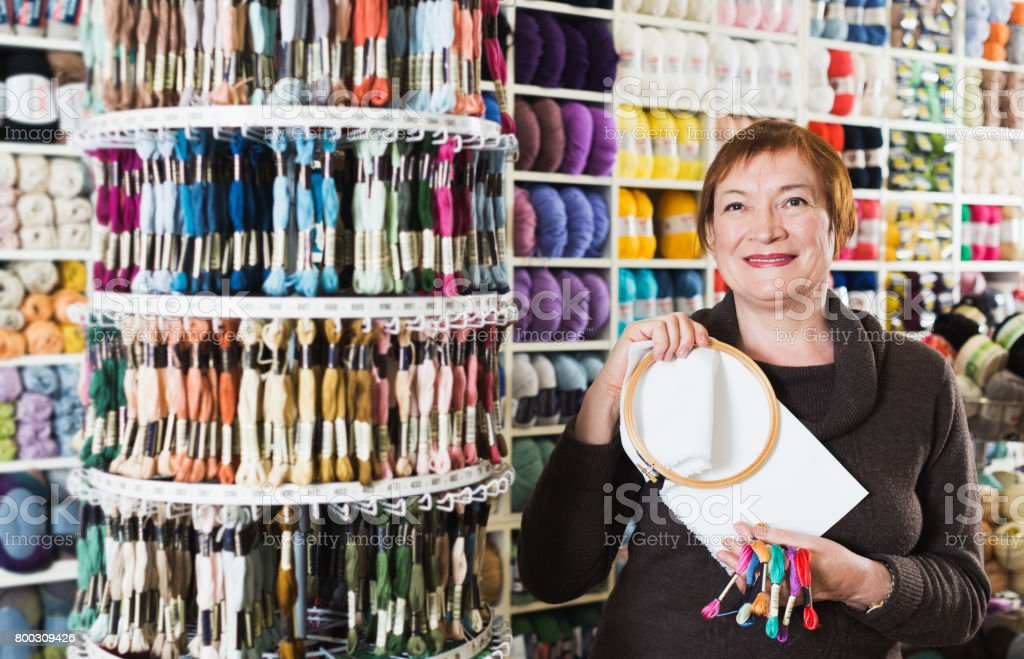 Woman buying embroidery accessories stock photo