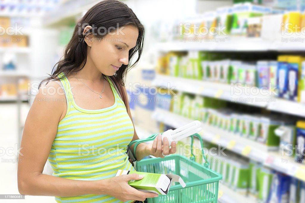 Woman buying energy-saving light bulb stock photo