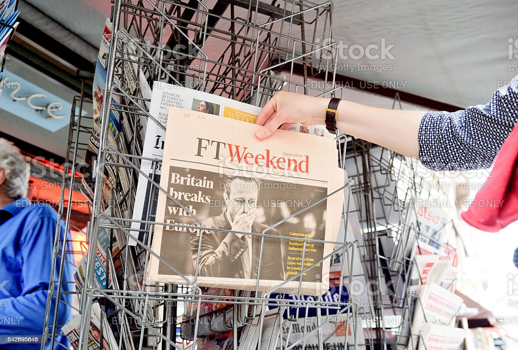 Woman buying Financial Times about Brexit stock photo