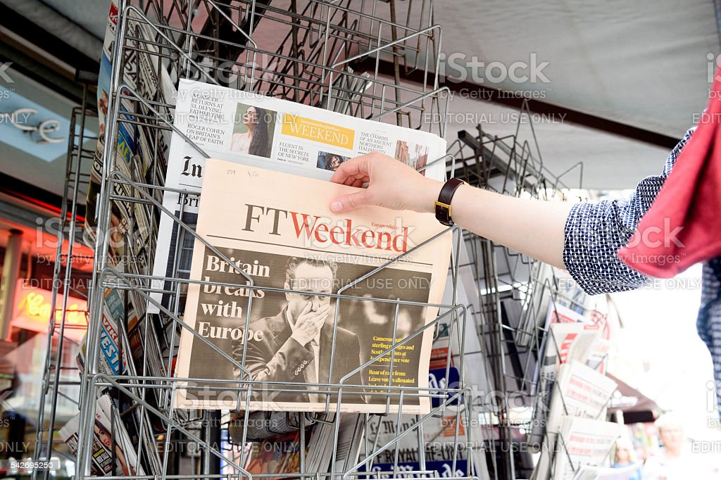 Woman buying Financial Times newspaper about Brexit stock photo