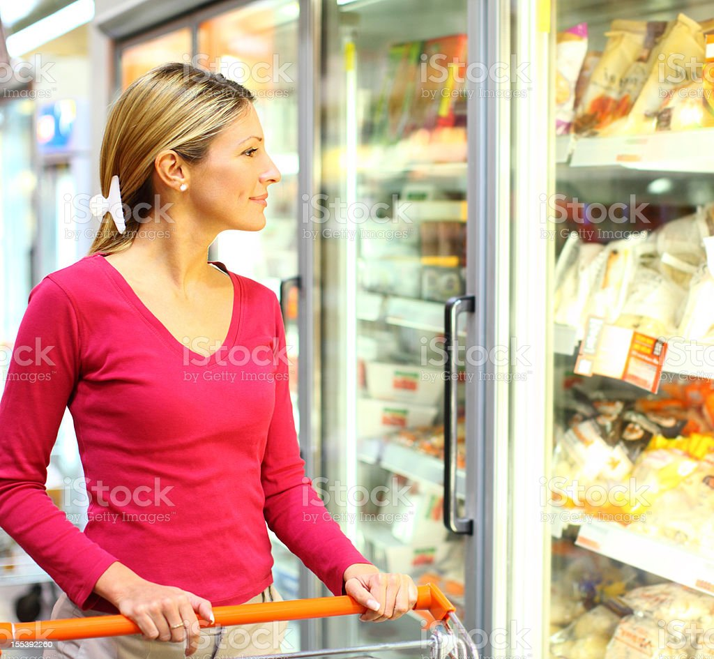 Woman buying food in local supermarket. stock photo