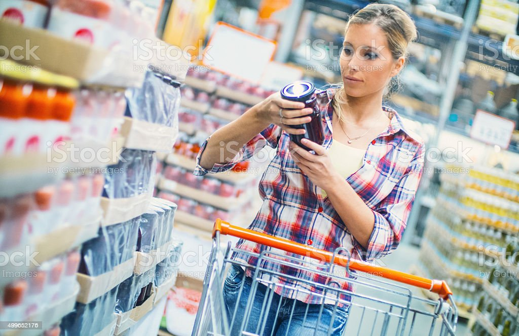 Woman buying food in supermarket. stock photo