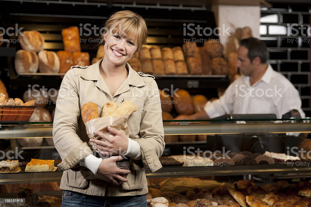 Woman buying fresh buns in bakery royalty-free stock photo
