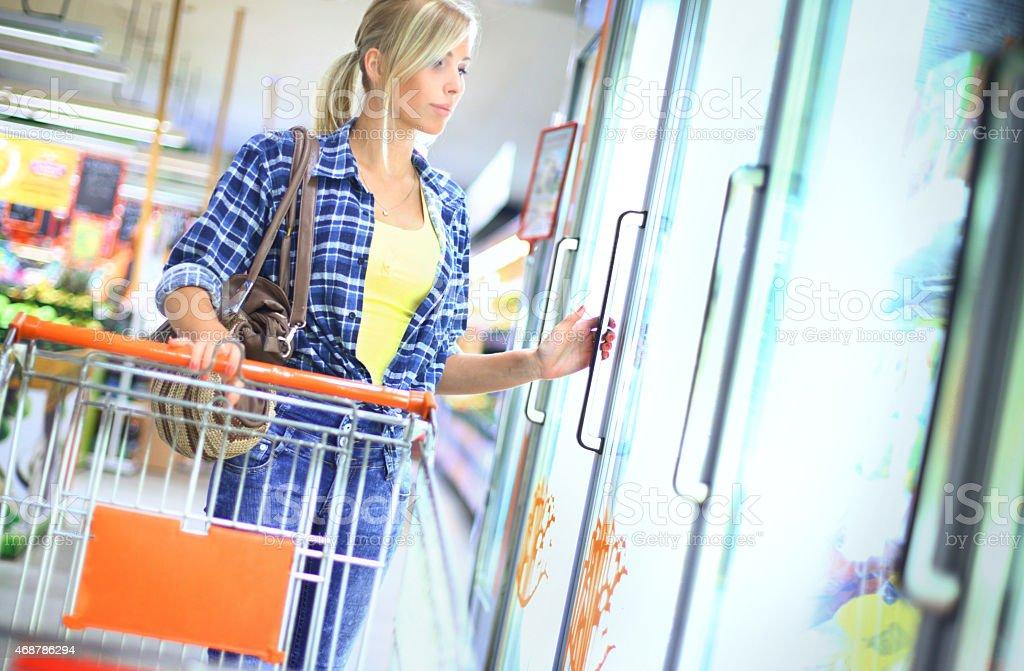 Woman buying frozen food in supermarket. stock photo