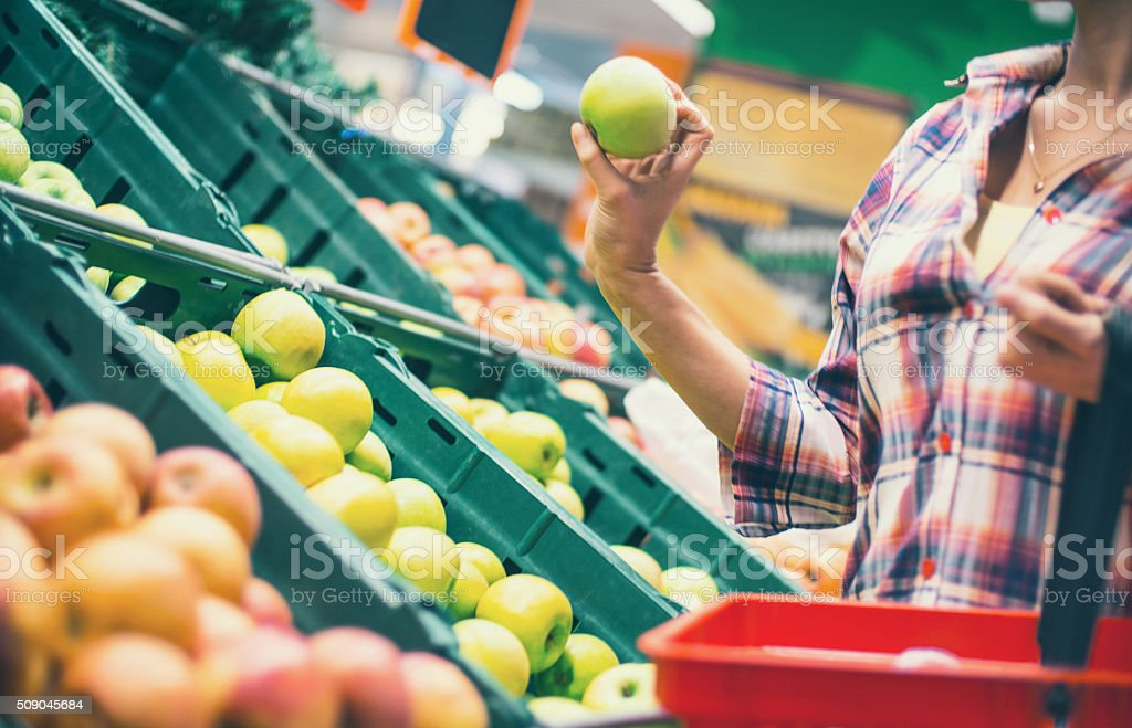 Woman buying fruit in supermarket. stock photo
